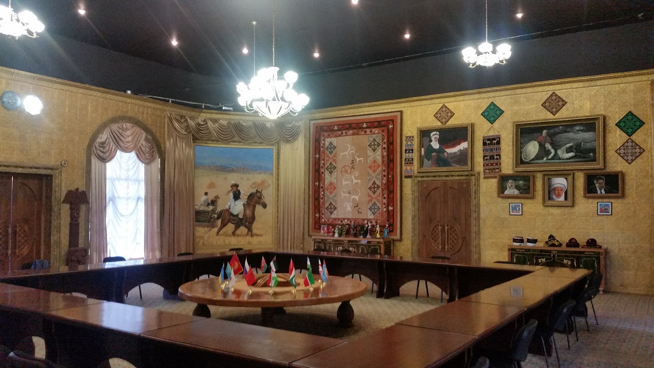 Some sort of presidential meeting room with Kyrgyz cultural things on the wall. The painting is about a famous love story